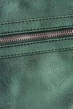 Grönt konstgjort läder med blixtlåset för bakgrund arkivfoton
