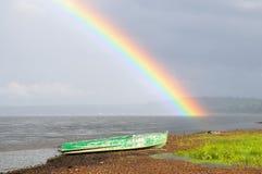 Grönt metallfartyg som står på styrbordsidan på bakgrunden av en ljus regnbåge över en bred flod Royaltyfria Foton