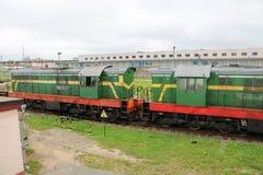 Grönt metalliskt järn rullade fraktdrevet, lokomotivet för vagnen av gods på stänger på järnvägsstationen royaltyfri bild