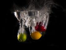 Grönt och rött äpple, gul citron som faller in i att plaska vatten på svart bakgrund arkivfoto