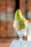 Grönt päron i höjdexponeringsglas Royaltyfri Bild