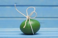 Grönt påskägg med den vita pilbågen på blå träbakgrund Royaltyfri Foto