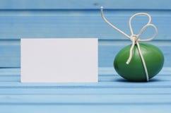 Grönt påskägg med den vita pilbågen på blå träbakgrund med det tomma kortet Royaltyfri Bild