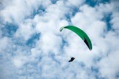 Grönt paragliderflyg i den blåa himlen mot bakgrunden av moln Royaltyfria Foton