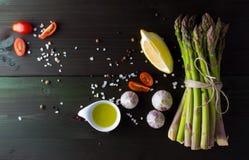 Grönt sparriers med vitlök, salt, citronen, den körsbärsröda tomaten, olivolja och peppar blandar på mörk bakgrund, bästa sikt Royaltyfri Bild