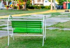 Grönt stål kopplar av stol parkerar in royaltyfri fotografi