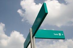Grönt taxitecken mot en blå himmel med moln Utrymme till det vänstert för text royaltyfria bilder