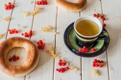 Grönt te, bagel och vinbär Arkivfoto