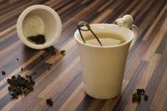 Grönt te i dekorerad tekopp på den wood tabellrengöringen Royaltyfri Bild