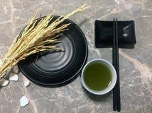 Grönt te i en kopp te och uppsättningen av den svarta maträtten med svarta pinnar Royaltyfri Fotografi