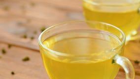 Grönt te med mintkaramellen, steg, gojibär och ananas i tekanna lager videofilmer