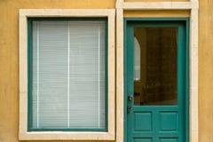 Grönt träfönster och dörr på den gula väggen Royaltyfri Bild