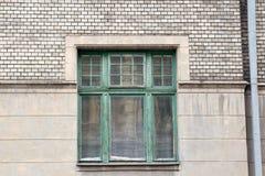 Grönt träfönster på en grå fasad av huset med en avrinning p arkivbilder