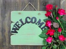 Grönt välkommet tecken för antikvitet med blommagränsen av röda rosor som hänger på lantlig wood bakgrund Arkivfoto