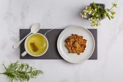 Grönt växt- vitt te med strikt vegetarianhavrekakor på vit backgr royaltyfria bilder