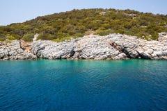 Grönt vatten för blått och för turkos av havshavet och kust av den obebodda ön royaltyfria bilder