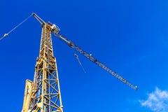 Grúa amarilla en un emplazamiento de la obra con el cielo azul Fotos de archivo