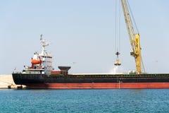 Grúa amarilla que descarga la arena del buque de carga grande del carguero en el puerto, numeración de la carga, eficacia del tra foto de archivo libre de regalías