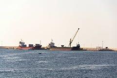 Grúa amarilla que descarga la arena del buque de carga grande del carguero en el puerto, numeración de la carga, eficacia del tra fotos de archivo libres de regalías