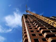 Grúa de construcción cerca del edificio en fondo del cielo azul Imagen de archivo libre de regalías