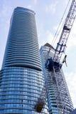 Grúa de construcción delante del rascacielos corporativo Fotografía de archivo