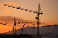 Grúa de construcción en el fondo de la puesta del sol Imagenes de archivo