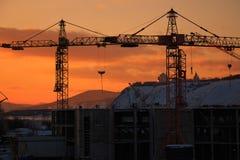 Grúa de construcción en el fondo de la puesta del sol Foto de archivo