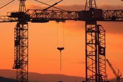 Grúa de construcción en el fondo de la puesta del sol Fotos de archivo