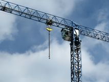 Grúa de construcción en el fondo del cielo azul nublado imágenes de archivo libres de regalías