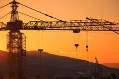 Grúa de construcción en el paisaje de la puesta del sol Fotos de archivo