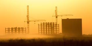 Grúa de construcción en la puesta del sol Imagen de archivo libre de regalías