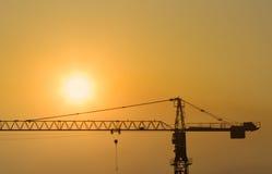 Grúa de construcción en la puesta del sol Fotos de archivo libres de regalías