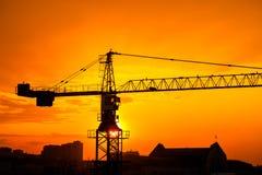 Grúa de construcción y siluetas industriales de los edificios sobre el sol en la salida del sol Foto de archivo libre de regalías