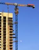 Grúa de la fachada y de construcción cerca del edificio concreto moderno bajo construcción foto de archivo