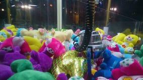 Grúa de la garra que desciende y que hace tentativa de agarrar el juguete, diversión en el parque de atracciones almacen de metraje de vídeo