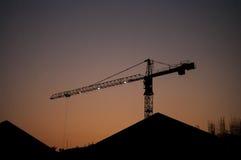 Grúa de la silueta con el cielo de la puesta del sol Fotos de archivo