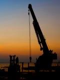 Grúa de la silueta que trabaja en el puerto Foto de archivo