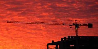 Grúa del edificio en fondo el cielo rojo Fotografía de archivo libre de regalías