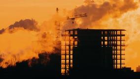 Gr?a del emplazamiento de la obra en el edificio en silueta retroiluminada de la hora de oro de la ciudad, de la salida del sol o almacen de metraje de vídeo