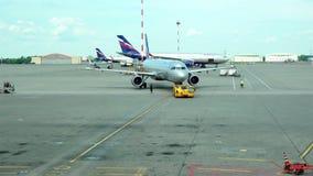 Grúa en un avión de pasajeros de carreteo del acoplamiento rígido en pista almacen de video