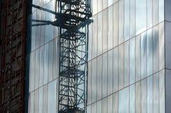 Grúa en un rascacielos en espejos imagenes de archivo