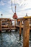 Grúa flotante que instala la viruta de madera para mantener los canales en Venecia, Italia imagenes de archivo