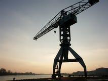 Grúa grande del puerto en la puesta del sol fotografía de archivo