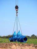 Grúa que maneja el tubo de 500m m con las válvulas de puerta Proceso de la construcción Foto de archivo libre de regalías