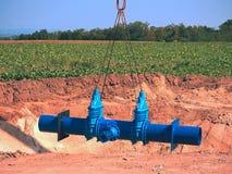 Grúa que maneja el tubo de 500m m con las válvulas de puerta Proceso de la construcción Fotografía de archivo