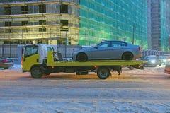 Grúa que transporta un coche en una calle de la ciudad fotos de archivo