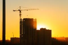 Grúa y rascacielos de construcción en la puesta del sol foto de archivo