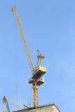 Grúas amarillas en emplazamiento de la obra con el cielo azul Foto de archivo