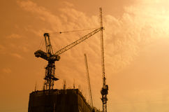 Grúas de construcción y siluetas industriales del edificio sobre el sol Fotos de archivo libres de regalías