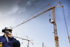 Grúas de construcción y trabajador del edificio Imagen de archivo libre de regalías